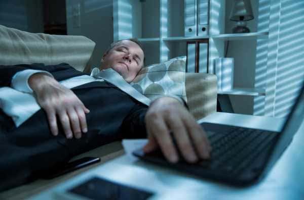 残業して帰って疲れ果てた男性の画像